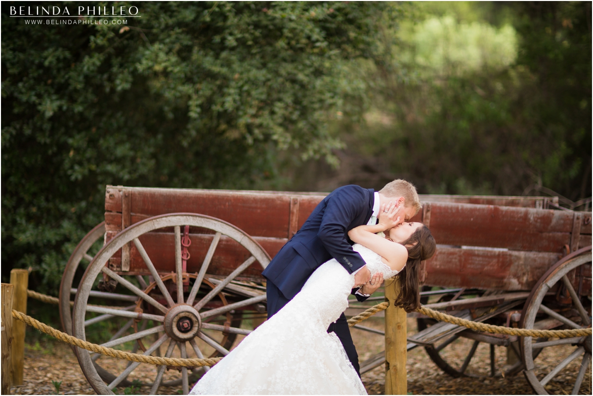 Bride and groom kiss near an antique wagon at Temecula Creek Inn wedding. Photos by Belinda Philleo