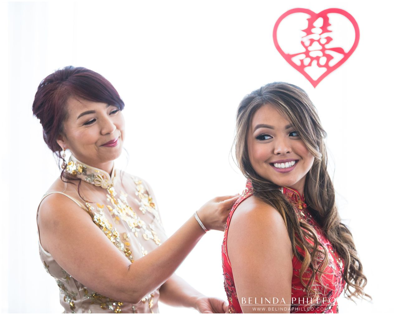 Mother of the bride zips up bride's qipao before the tea ceremony