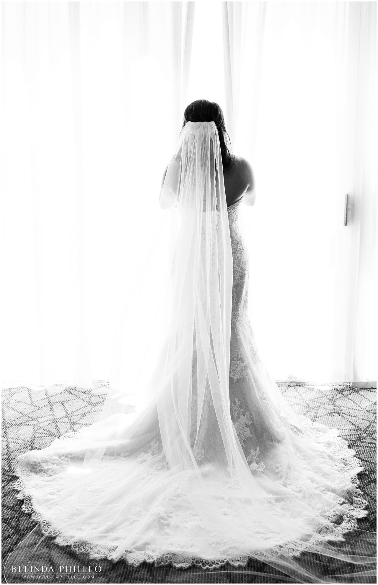bride wearing her maggie sottero gown looks out the window before the ceremony