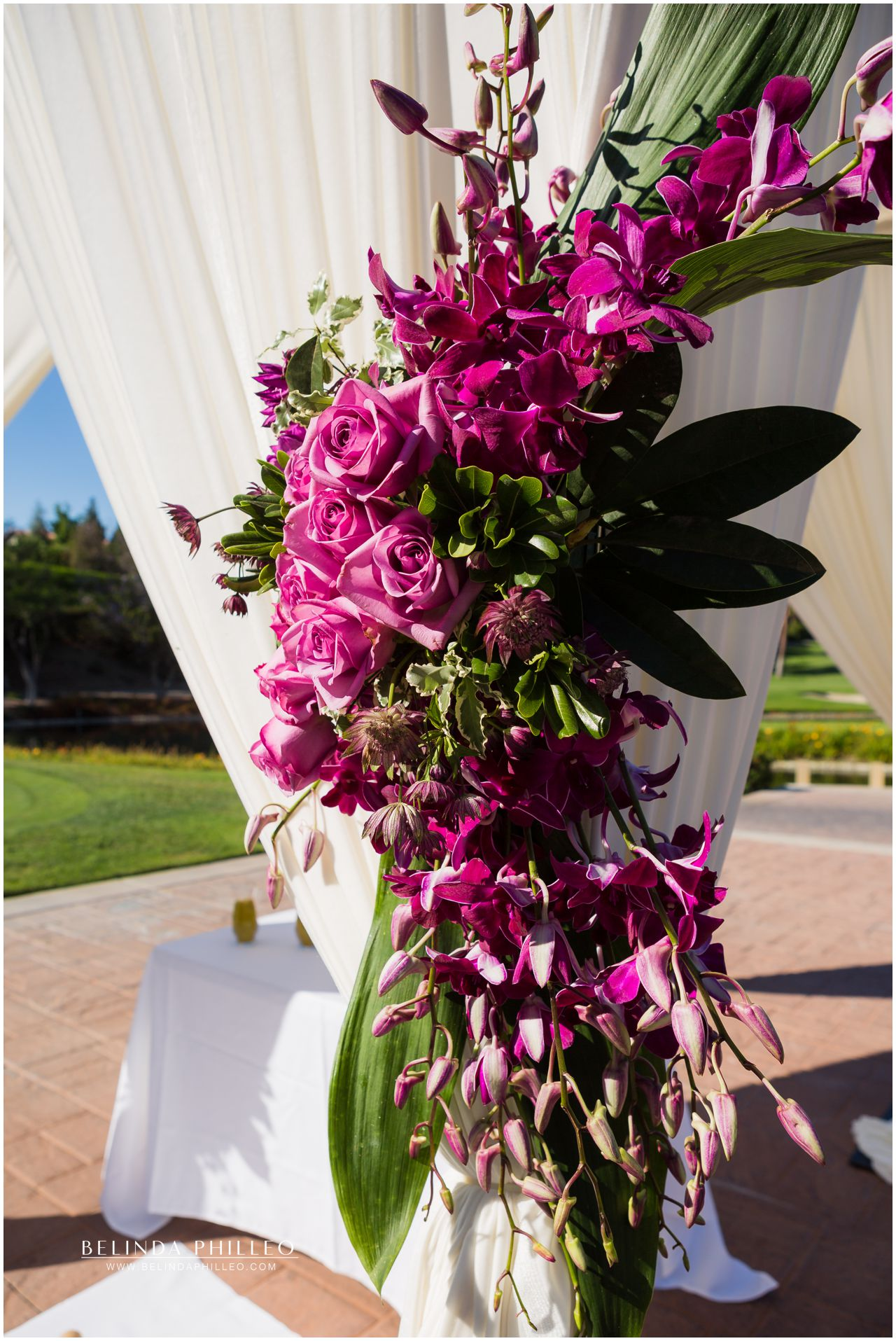 Purple and fuscia roses and orchids decorate wedding ceremony at Friendly Hills Country Club, Whittier, CA