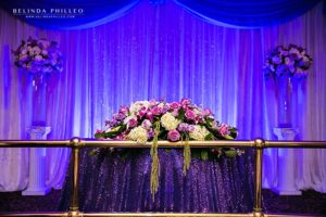 White and purple head table flowers by Creative Celebration Events, Paramount, CA