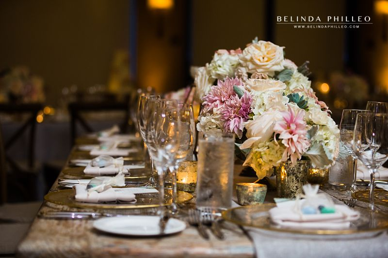 White and pink flowers adorn rustic tables for wedding reception at The Ranch Laguna