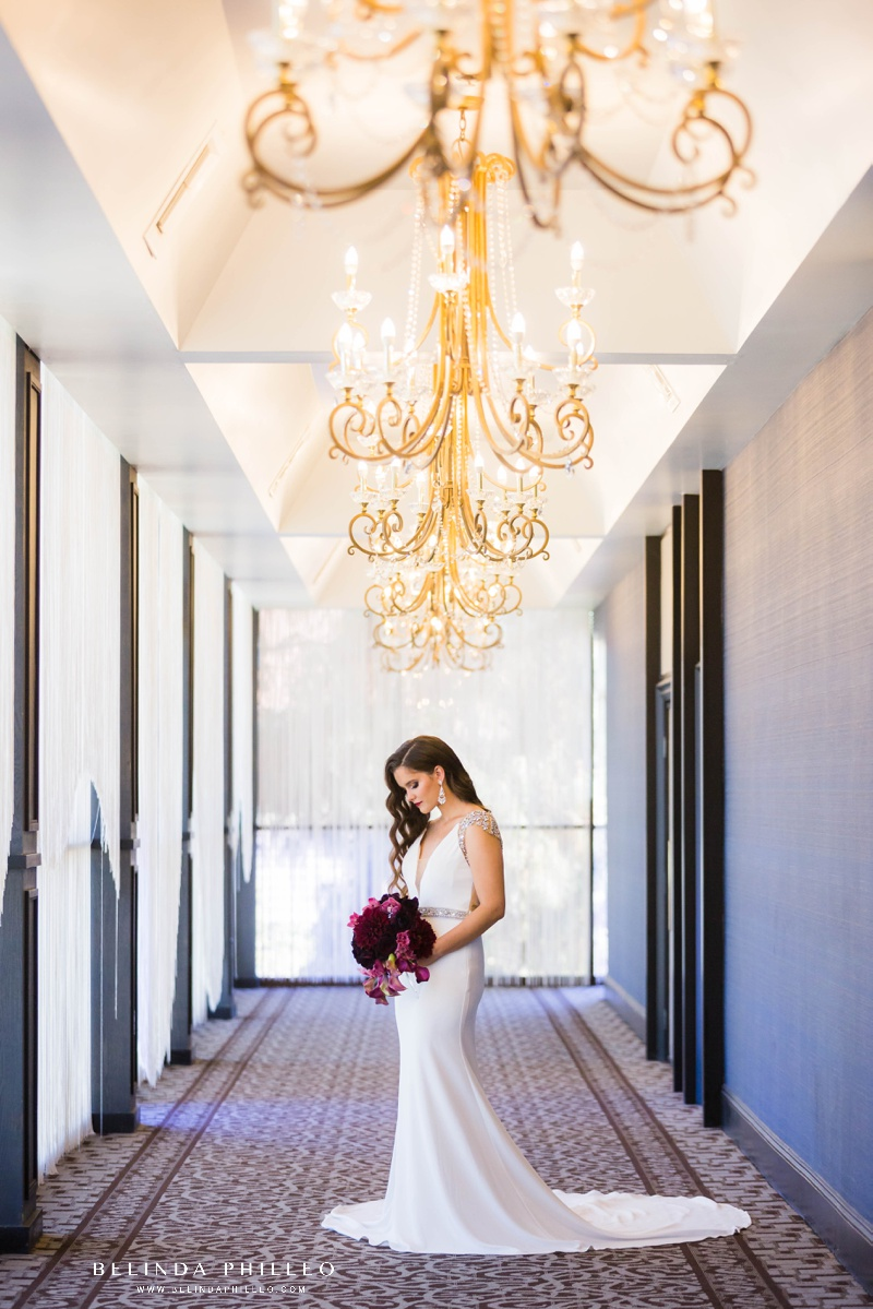 Bride admires her bouquet in a hallway of chandeliers at The Hills Hotel Laguna