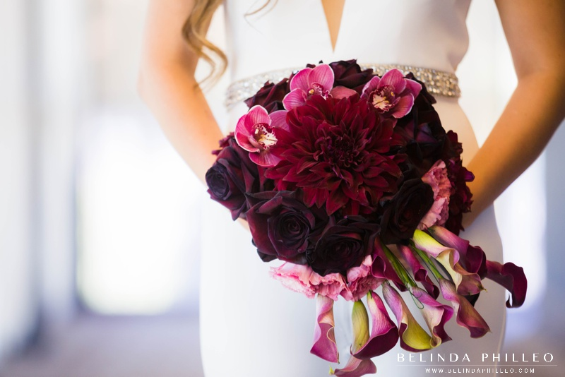 Modern Monochrome bridal bouquet made of merlot colored roses, lilies and orchids.