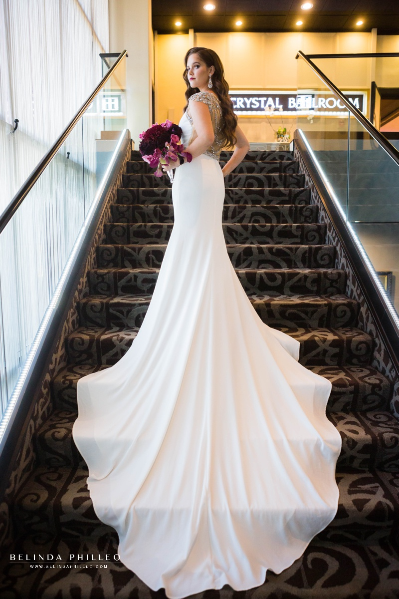 Bride shows of her Calla Blanche bridal gown on the staircase at The Hills Hotel Laguna