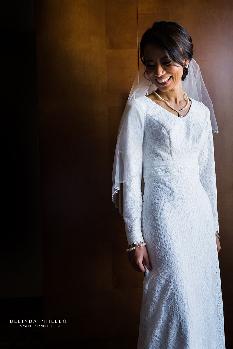 Glowing bride shows off her Modest by Mon Cheri wedding gown from The Hitching Post