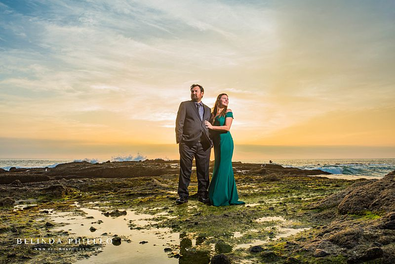 Engagement session locations in Orange County. A couple in formal attire poses for sunset photos on Victoria Beach, CA during their engagement session.