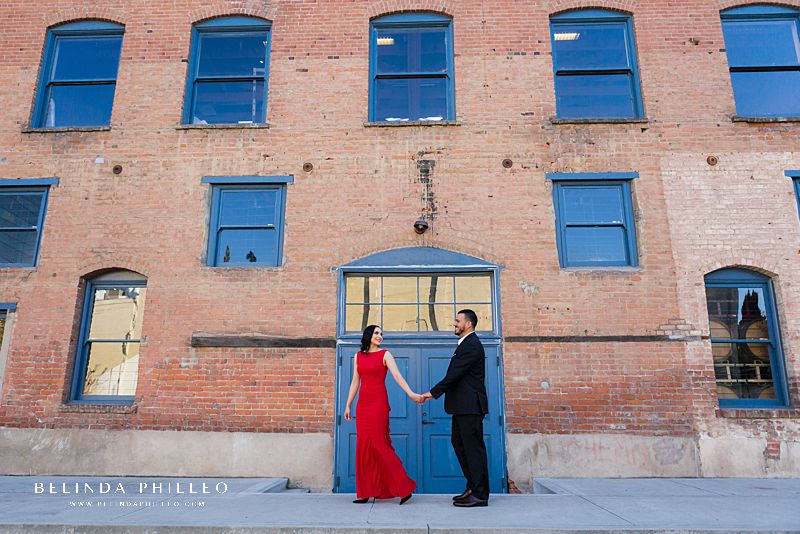 Engagement locations in Orange County, CA. A couple in formal attire poses for a photo in an alleyway in Downtown Santa Ana during their engagement session.