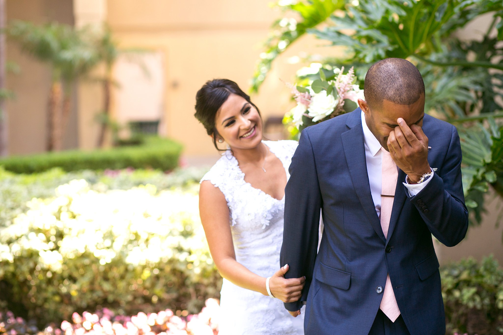Emotional wedding photos: The groom turns away and cries during the first look with his beautiful bride.