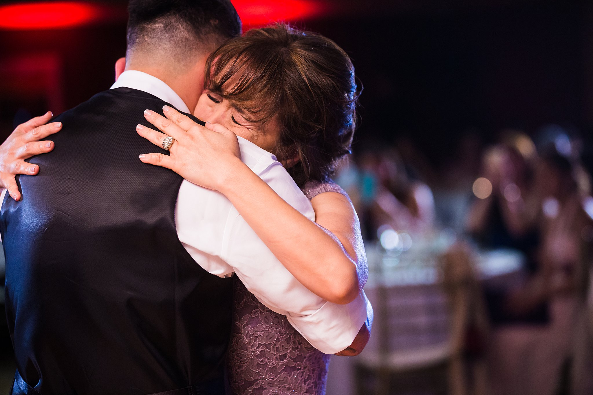 Emotional wedding photos. Mother of the groom cries on son's shoulder during the mother-son dance.