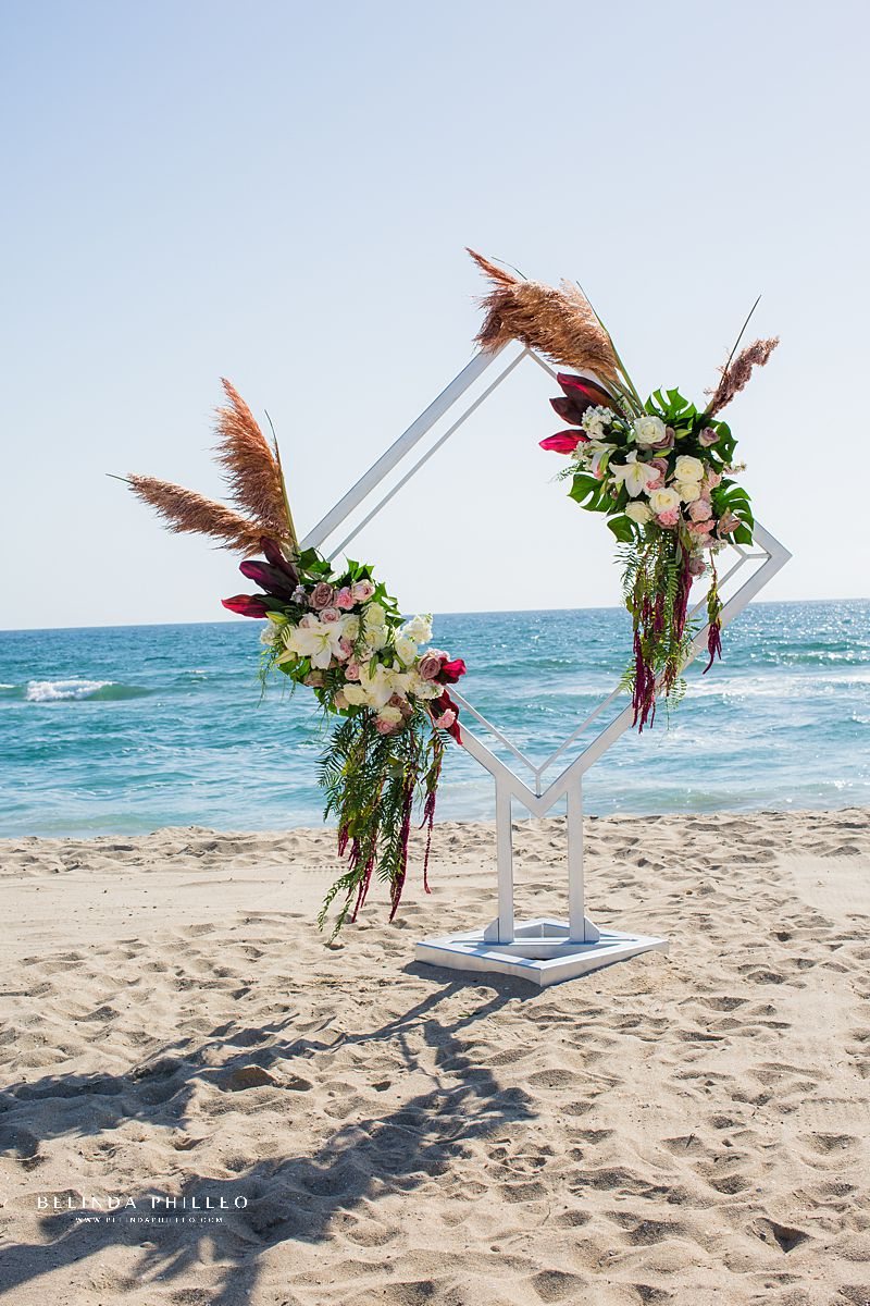 Bespoke wedding ceremony arch in Huntington Beach, CA created by Serenade of Flowers. Photo by Belinda Philleo