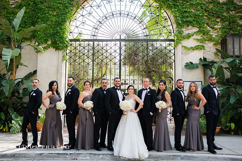 Bridal party poses in front of stunning gate at Los Angeles River Center & Gardens. Bride's gown is Martina Liana in Carmen + Sander style. Bridesmaids wearing White by Vera Wang v-wire crepe mermaid in Charcoal