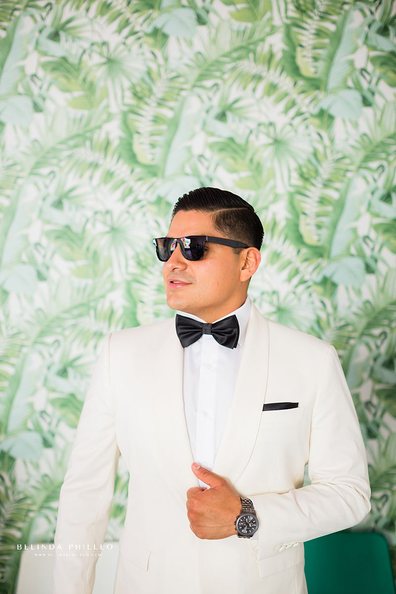 Custom white tux and black bowtie for groom at his Los Angeles Wedding. Photography by Belinda Philleo