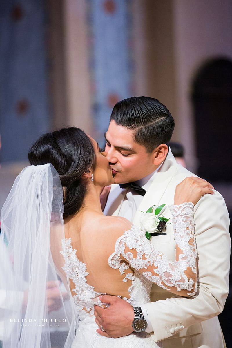 Bride and groom share first kiss during their Los Angeles wedding. Gown by Martina Liana, photo by Belinda Philleo