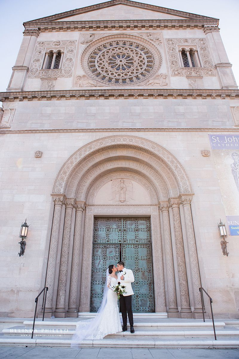 Bride and groom share a kiss on the front steps of St John's Cathedral in Los Angeles, CA. Photography by Belinda Philleo