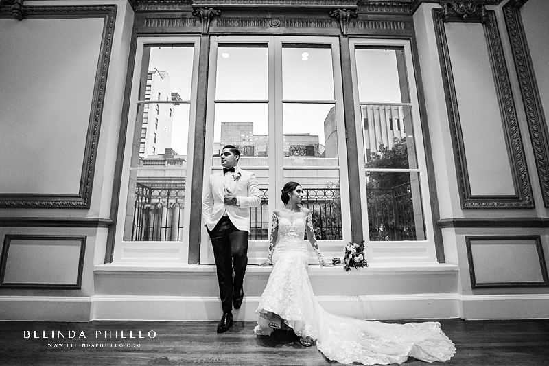 Newly weds pose for a photograph during their wedding at Alexandria Ballrooms in Los Angeles, CA. Photo by Belinda Philleo