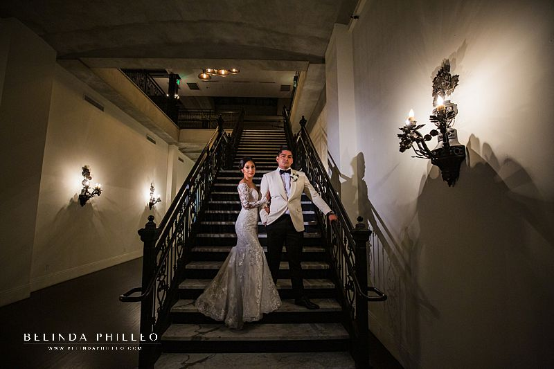 Los Angeles wedding photography: Bride and groom pose on staircase during their wedding at Alexandria Ballrooms, Los Angeles, CA. Photography by Belinda Philleo