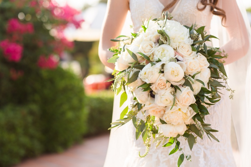 Bride shows off her dramatic bouquet of white peonies and blush roses at Hummingbird Nest Ranch